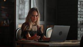 Freelancerkvinnan som arbetar med en bärbar dator i en coffee shop, stänger sig upp sikt stock video