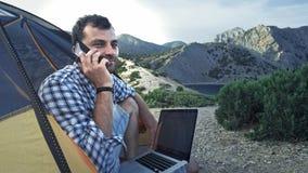 Freelancerman som arbetar genom att använda bärbara datorn som sitter i ett campa tält på stranden phone samtal Freelancer som ar arkivfilmer