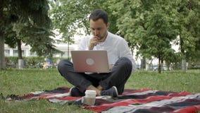 Freelancermannen med bärbara datorn på sommar parkerar på ljus dag Man i tillfälligt arbete på hans anteckningsbok och sammanträd royaltyfria bilder
