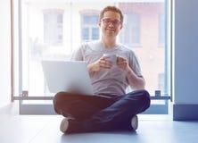 Freelancermens die laptop computer en kop van koffie gebruiken Royalty-vrije Stock Afbeeldingen