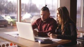 Freelancers novos homem e mulher que sentam-se em um café e que trabalham para um portátil filme