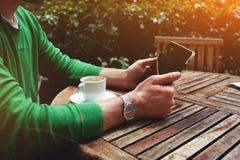 Freelancersammanträde på terrassen med kopp kaffe- och pekskärmminnestavlan, medan ha ett avbrott arkivbild