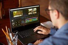Freelancervideoredaktören arbetar på bärbar datordatoren med film som redigerar programvara Videographer vlogger eller bloggerkam arkivfoto