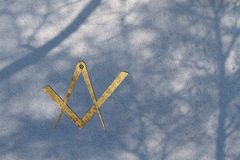 Freemason square and compasses symbol. Hi-res Freemason square and compasses symbol as golden embossing on a light blue wall with shadows of trees Stock Images