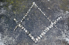 Freemason symbol. Made from stones on the ground Stock Photo