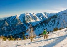 Freeride挡雪板滑下来一个陡坡在黎明 免版税库存图片