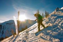 Freeride挡雪板滑下来一个陡坡在黎明 库存图片