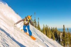 Freeride挡雪板滑下来一个陡坡在黎明 免版税图库摄影