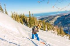 Freeride挡雪板滑下来一个陡坡在黎明 库存照片