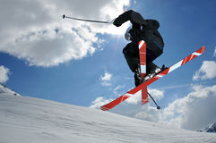 Freeride. A free-ride ski jumper, with skis crossed against a blue sky with clouds Stock Photos