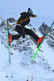 Freeride Jump. A freerider on skis performs a jump with legs spread forwards and backwards Royalty Free Stock Photo