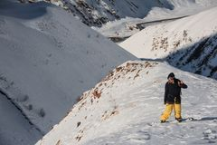 Freeride male snowboarder standing on the mountain peak. Covered with snow on the sunny day Stock Image