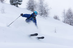Freeride skier skiing in deep powder snow. Extreme freeride skier skiing on fresh powder snow in forest downhill at winter season Royalty Free Stock Image