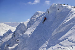 Freeride skiing with blue sky. Freeride skiing with peaks in the background and clear blue sky Stock Photography
