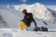 Freeride snowboarder with a board on the background of mountains. Freeride snowboarder with a board on the background of high snowy mountains on sunny day Royalty Free Stock Images