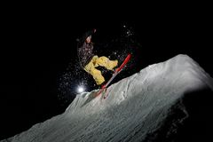 Snowboarder with dreadlocks dressed is jumping in in the mountains at night. Freeride snowboarder with dreadlocks dressed in the yellow sportswear is jumping in Stock Photo