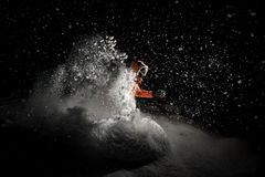 Freeride snowboarder jumping in snow at night. Freeride snowboarder dressed in the orange sportswear and glasses jumping in powder snow at night stock photos
