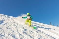 Freeride snowboarder glijdt onderaan een steile helling bij dageraad Stock Foto's