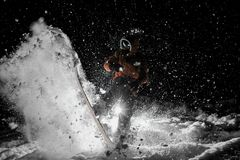 Freeride snowboarder jumping on the board in snow at night. Freeride snowboarder dressed in the orange sportswear and glasses jumping on the board in powder snow stock photos