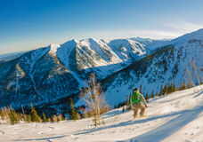 Freeride snowboarder slides down a steep slope at dawn.  Royalty Free Stock Image