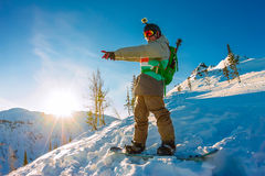 Freeride snowboarder stands on hillside at dawn and shows his ha. Nd forward Stock Photos