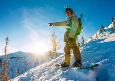 Freeride snowboarder stands on hillside at dawn and shows his ha. Nd forward Royalty Free Stock Photography