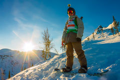 Freeride snowboarder stands on hillside in light dawn sun.  Royalty Free Stock Photos
