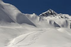 Freeride trails on the slopes of the Caucasus. Freeride tracks on pure white snow. High slopes of the ridge. Clear blue sky on a sunny winter day. Sharp peaks of Stock Images