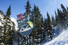 Freerider banhoppning för Snowboarder från en snöramp i solen på en bakgrund av skogen och berg Arkivbild