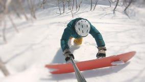 Freerider climbing up, holding boards, filmed on the gopro hero 8 black, frame shot on a freeride tour in Kamchatka