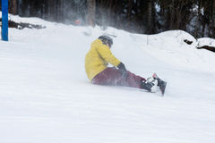 Freerider falling down the slope. Male snowboarder falls on the slopes during the descent Royalty Free Stock Photo