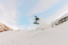 Freerider is jumping in the snow spray from the slope.  Stock Photography