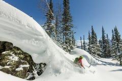 Freerider skiër springt van een rots van sneeuw in bomen in de bergen royalty-vrije stock fotografie