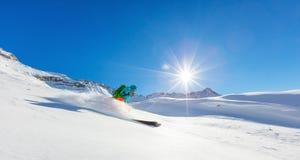 Freerider skier running downhill. In beautiful Alpine landscape. Fresh powder snow, blue sky on background Stock Images