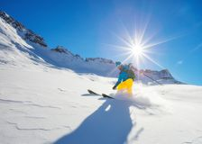 Freerider skier running downhill. In beautiful Alpine landscape. Fresh powder snow, blue sky on background Royalty Free Stock Images