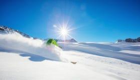 Freerider skier running downhill. In beautiful Alpine landscape. Fresh powder snow, blue sky on background Stock Photo