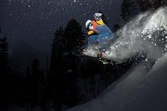 Freerider snowboarder doskakiwanie przy nocą z trampoliną w lesie Fotografia Royalty Free