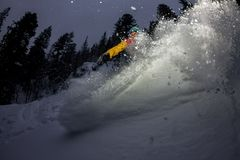 Freerider snowboarder jumping at night with a springboard in the forest Royalty Free Stock Photography