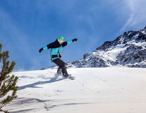 Snowboarder moving down. Freerider snowboarder moving down in snow powder Royalty Free Stock Image