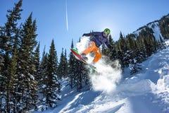 Freerider Springen des Snowboarders von einer Schneerampe in der Sonne auf einem Hintergrund des Waldes und der Berge Lizenzfreie Stockfotos