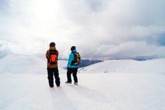 2 freeriders на горном пике ища совершенная линия для езды Стоковое Фото