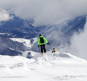 Freeriders on off-piste slope and mountains in haze Royalty Free Stock Photo