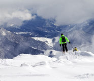 Freeriders on off-piste slope and mountains in mist Royalty Free Stock Image