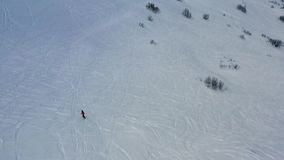 freeriding在新鲜的粉末雪的小山下的一个人的空中英尺长度,4k 股票视频