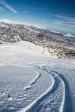 Freeriding in the alpine arc. Free ride ski tracks on snowy slope. Oblique shot taken from above in the italian Alps. Old ski resort now used for back country Royalty Free Stock Images