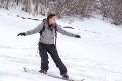 Freeriding av en kvinnlig snowboarder Fotografering för Bildbyråer