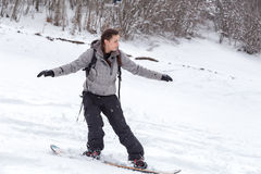 Freeriding of a female snowboarder. Female snowboarder is having fun to ski with her snowboard on the snowy ground during a snowy day Stock Image