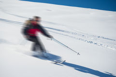 Freeriding on fresh powder snow, blurred motion. One person skiing downhills off piste on snowy slope in the italian Alps, with bright sunny day of winter season Stock Photos