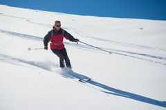 Freeriding on fresh powder snow. One person skiing downhills off piste on snowy slope in the italian Alps, with bright sunny day of winter season. Thick Powder Royalty Free Stock Photos