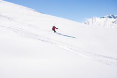 Freeriding on fresh powder snow. One person skiing downhills off piste on snowy slope in the italian Alps, with bright sunny day of winter season. Thick Powder Royalty Free Stock Photo